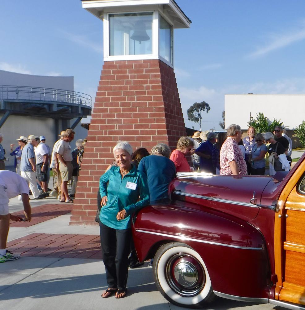 Linda Benson posing by woody station wagon