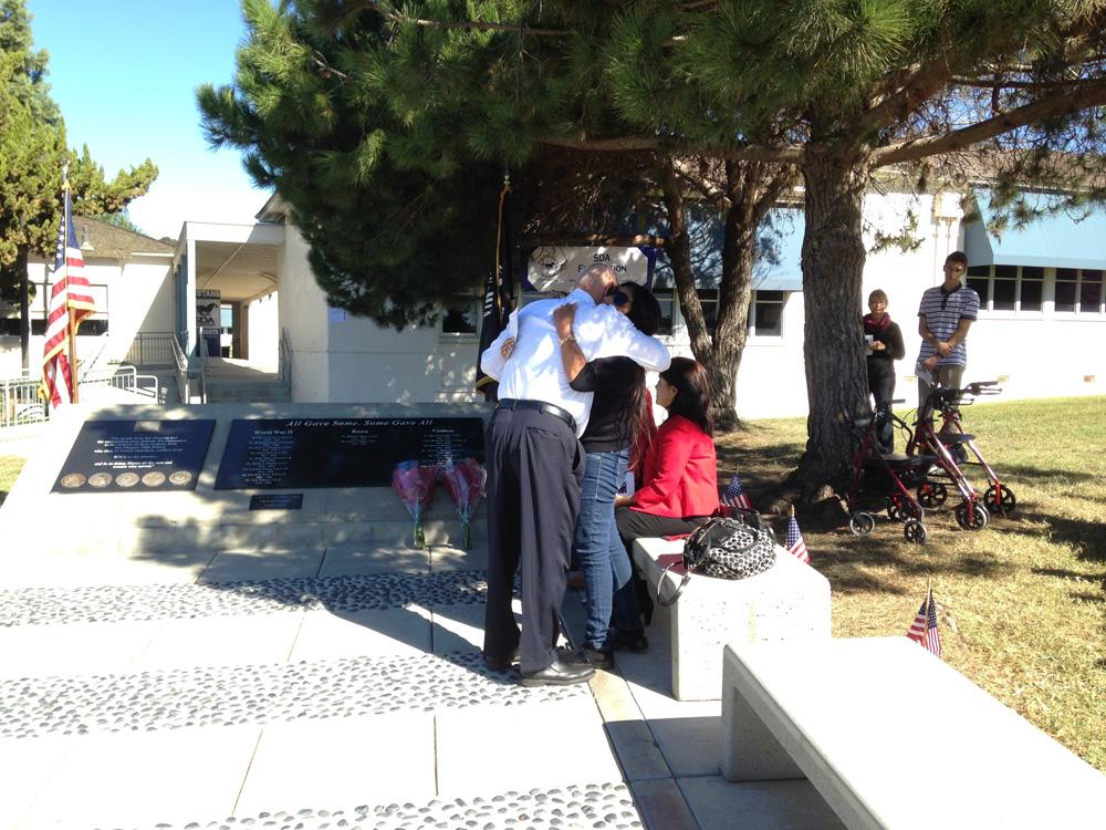 Solomon hugging Helen next to the Fallen Alumni memorial