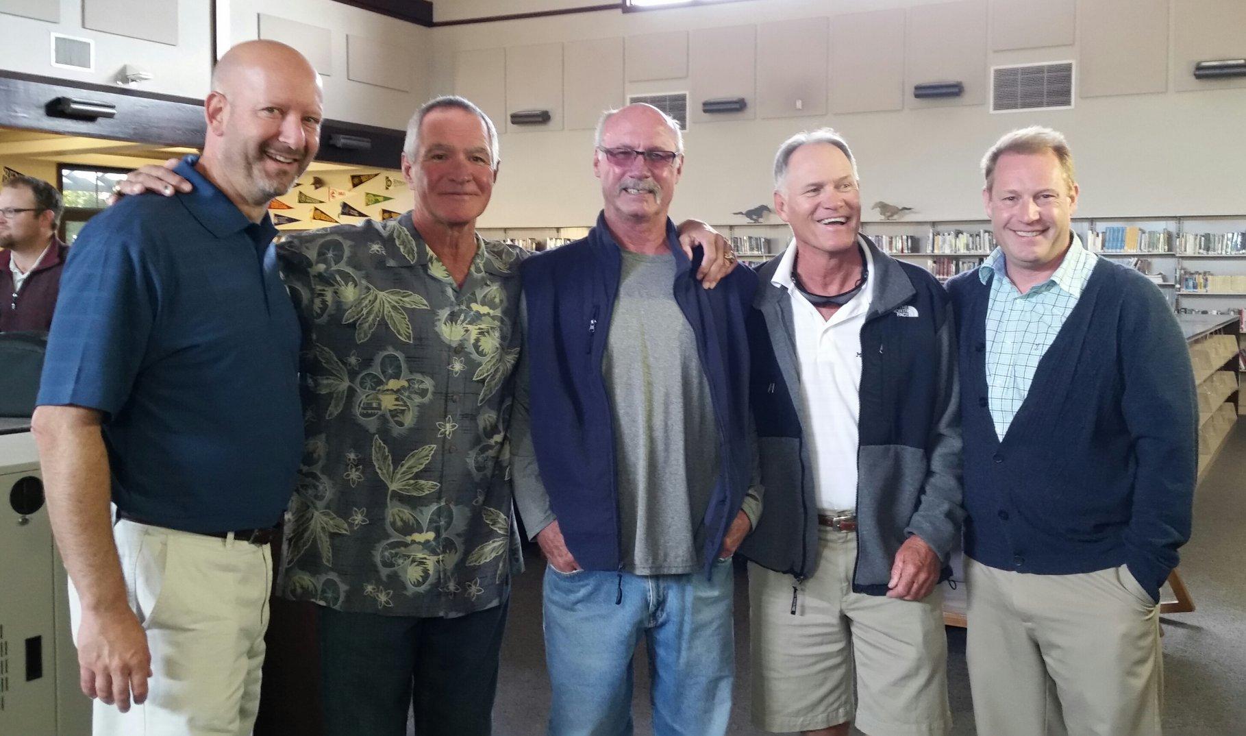 Five men smile for the camera