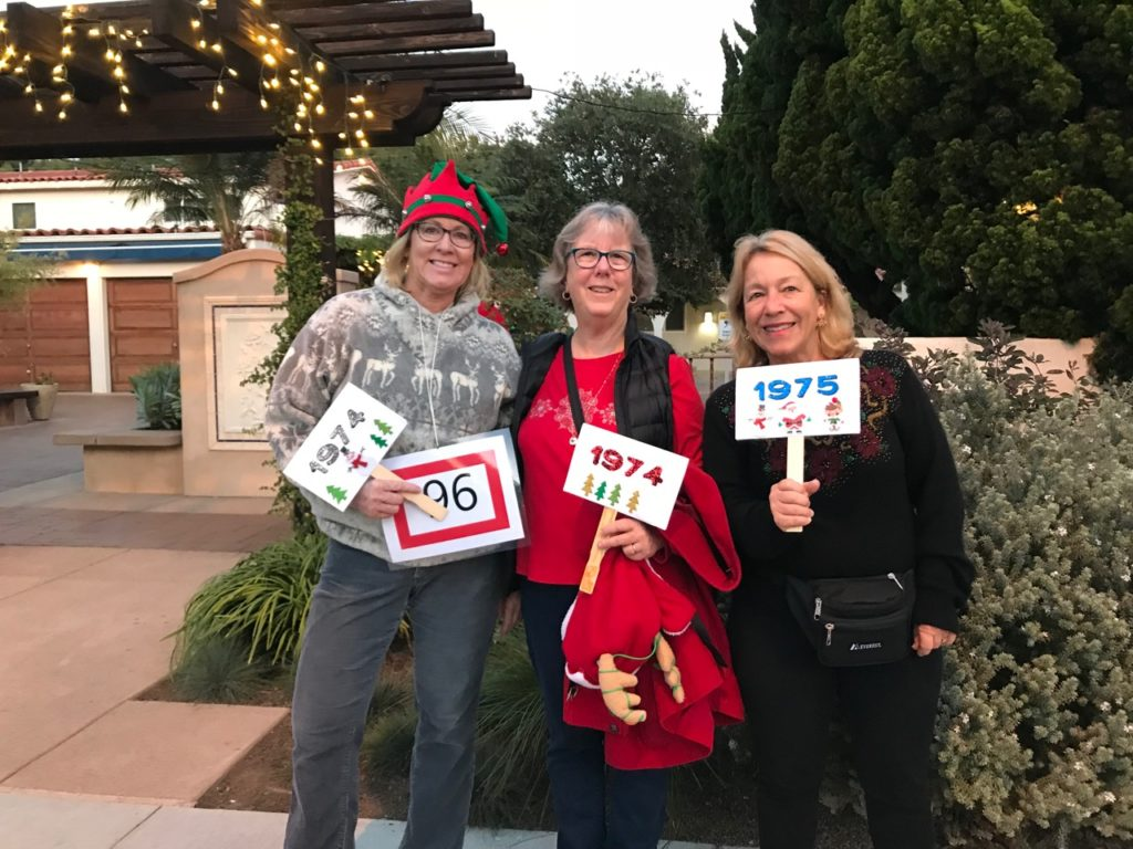 Robynn, Maureen and Lori, holding class signs