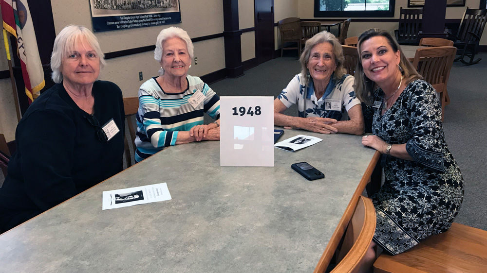 Four women smile at table with a sign that says 1948