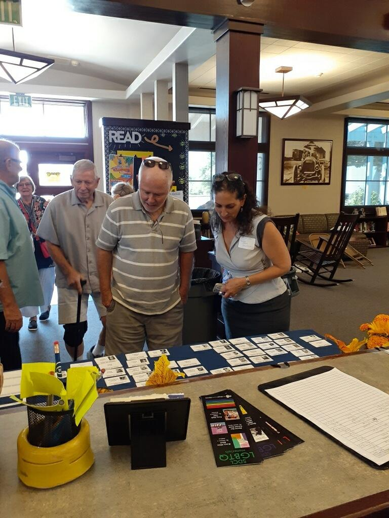 Alumni look over table with badges