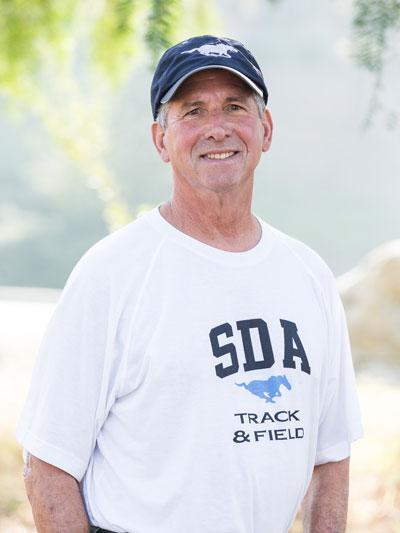 Hank smiles at the camera wearing SDA t-shirt